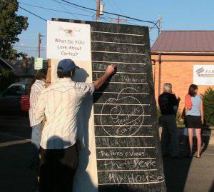 Man drawing on chalkboard outside