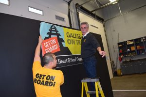 Fire Chief Tom Simkins, on right, hangs a banner at a Community Summit for Galesburg on Track