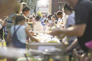 Residents sample a potluck meal in downtown Meadville, Pennsylvania. The event, which drew hundreds, was a celebration of the city's Community Heart & Soul project, My Meadville, on 7-27-18. Image credit: Shannon Roae, The Meadville Tribune.
