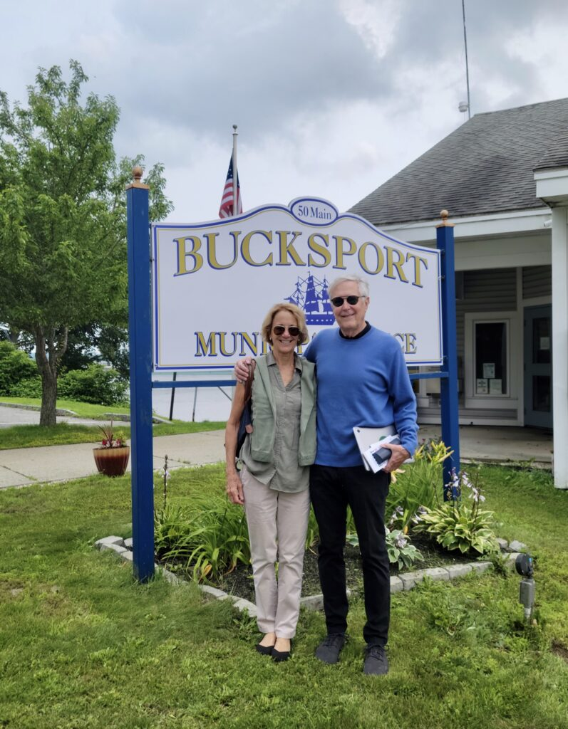 Deb and Jim Fallows in front of Bucksport Maine town sign